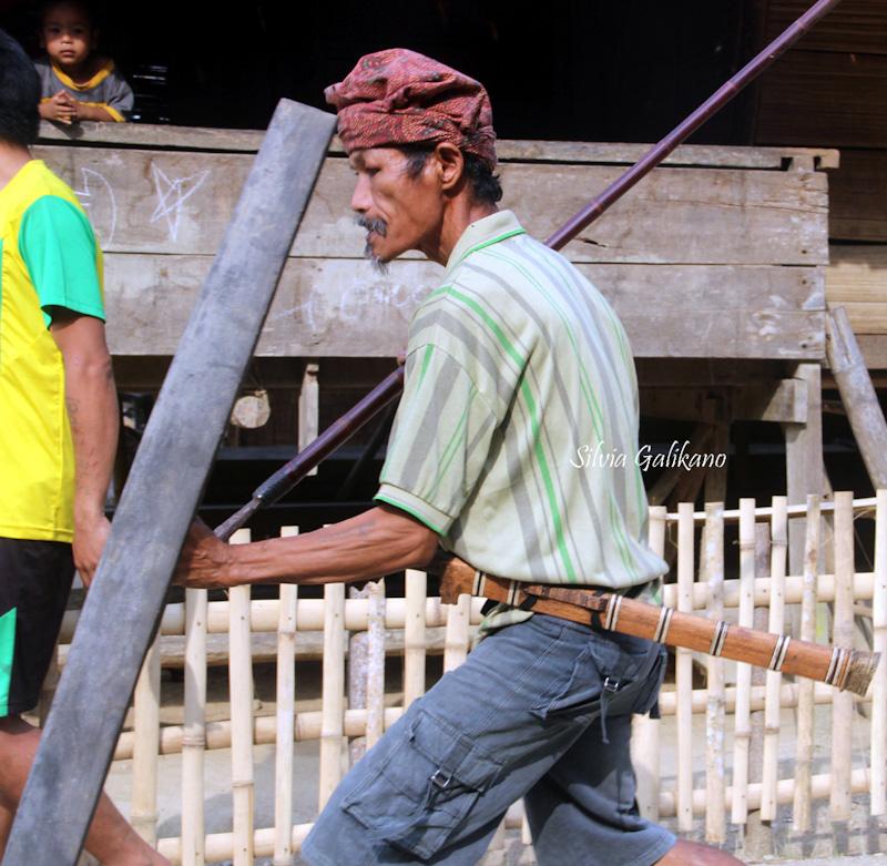 Sado Taringolu memegang tombak dan perisai. Guma terikat di pinggang, 2015. (Foto Budi-Karsa Institute)